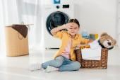 fáradt gyermek sárga inget és farmert ül kosár közelében a mosodában medve játék