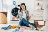 Müde Frau sitzt auf dem Boden neben verstreuten Kleidungsstücken und Körben in Waschküche