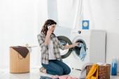 Fotografie Frau stellt Kleidung in Waschmaschine und telefoniert mit Smartphone in Waschküche