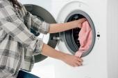 Ausgeschnittene Ansicht einer Frau, die Kleidung in Waschmaschine in Waschküche legt