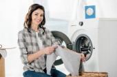 nő a mosodában ruhákat csavaralátét közelében lévő