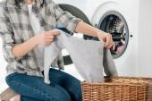 Fotografie Ausgeschnittene Ansicht einer Frau, die Kleidung in der Waschküche in der Nähe der Waschmaschine hält
