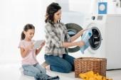 Fotografie Mutter hält Kleidung in der Nähe in der Waschmaschine, Tochter in rosa T-Shirt sitzt mit digitalem Tablet in Waschküche