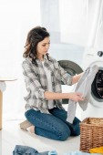 Fotografie Frau im grauen Hemd und Jeans halten Kleidung in der Nähe von Waschmaschine in Waschküche