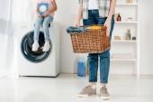 Fotografie abgeschnittene Ansicht der Tochter auf Waschmaschine sitzend mit Waschpulver wile Mutter hält Korb in Waschküche
