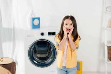 frightened child in yellow shirt and jeans standing in laundry room