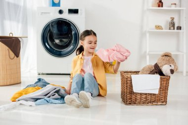 child in yellow shirt and jeans sitting and putting clothes to basket in laundry room