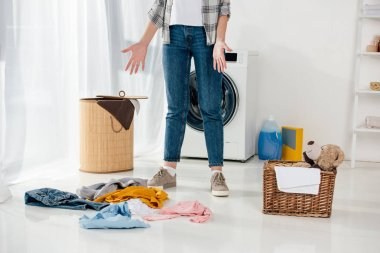 cropped view of woman standing near baskets and scattered clothes on floor in laundry room