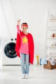 Fotografie Kind im roten hausgemachten Superheldenanzug in der Waschküche