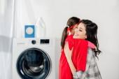 Fotografie Mutter umarmt Tochter im roten hausgemachten Anzug mit Sternzeichen in der Waschküche