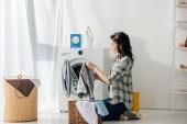 Fotografie Frau in grauem Hemd und Jeans legt Kleidung in Korb neben Waschmaschine in Waschküche