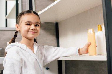 cute child in white bathrobe taking shower gel from shelf in bathroom