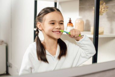 selective focus of child in white bathrobe looking to mirror and brushing teeth in bathroom