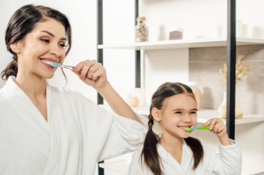 mother and daughter in white bathrobes brushing teeth with toothbrushes in bathroom