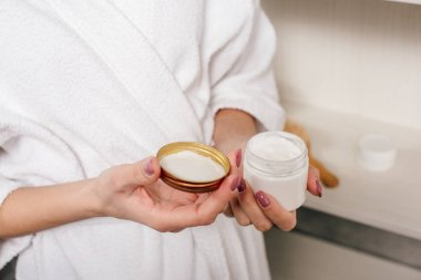 cropped view of woman holding container with cosmetic cream in bathroom
