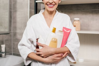 cropped view of woman in white bathrobe holding bottles in bathroom