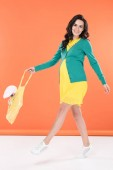 Photo Beautiful brunette pregnant woman holding string bag with toy rabbit on orange background