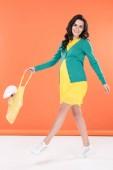 Fotografia Bella donna incinta bruna che tiene sacchetto di stringa con coniglio giocattolo su priorità bassa arancione
