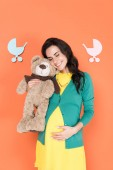 Happy pregnant woman holding teddy bear and touching belly with closed eyes on orange background