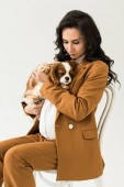 Photo Curly pregnant woman sitting on chair and holding dog isolated on white