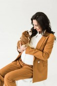 Photo Laughing pregnant woman in brown suit looking at dog isolated on white