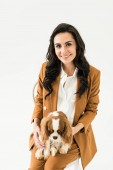 Photo Glad brunette woman in brown suit holding dog and smiling isolated on white