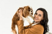 Photo Cheerful brunette woman in brown jacket holding dog isolated on white