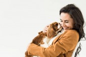 Photo Happy laughing girl in brown jacket holding dog isolated on white