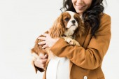 Photo Cropped view of laughing pregnant woman in brown jacket holding dog isolated on white