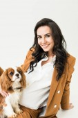 Photo Attractive pregnant woman in brown jacket stroking dog on white background