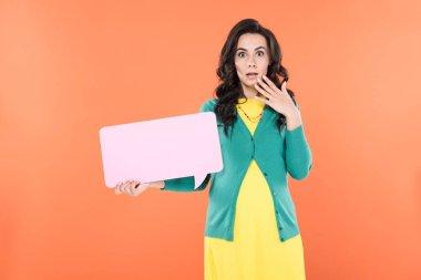 Shocked brunette pregnant woman holding speech bubble isolated on orange