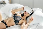 boldog barna nő a fehérnemű viselése virtuális-valóság sisak ágyon fekve