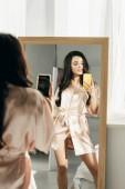 Fotografie attraktive brünette Frau fotografiert, während sie in der Nähe von Spiegel steht