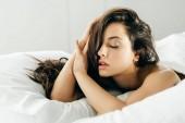sexy bruneta žena se zavřenýma očima, ležící na posteli doma