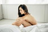 nackte brünette junge Frau sitzt auf dem Bett im modernen Schlafzimmer