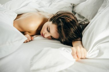 Selective focus of naked brunette girl lying on bed with closed eyes stock vector