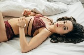 Photo brunette young woman in lace lingerie lying on bed with handcuffed hands