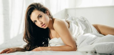panoramic shot of beautiful girl lying on bed in white modern bedroom ac