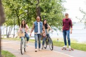 Photo handsome african american man walking near pretty girls riding bicycles and cheerful friend longboarding in park