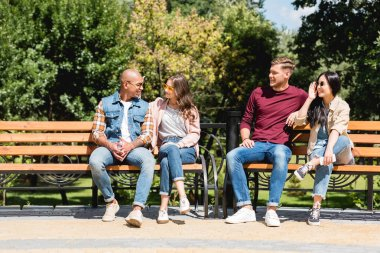 cheerful multicultural friends sitting on benches in park