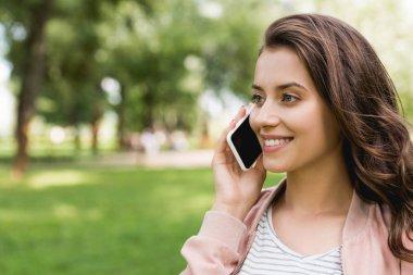 Attractive girl talking on smartphone in park stock vector