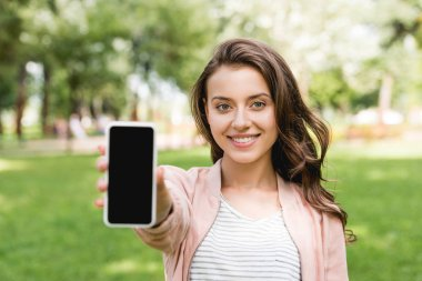 Selective focus of attractive girl holding smartphone with blank screen stock vector