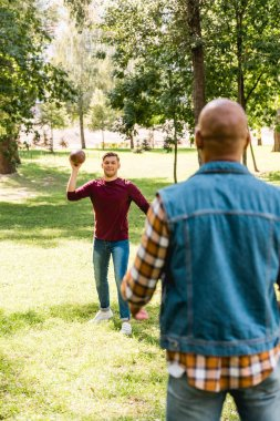 back view of african american man looking at happy friend throwing american football in park