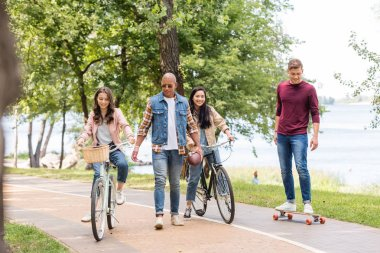 handsome african american man walking near pretty girls riding bicycles and cheerful friend longboarding in park