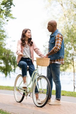 Happy african american man looking at cheerful girlfriend riding bicycle stock vector