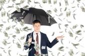 successful businessman in suit with umbrella gesturing under money rain