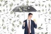 úspěšný podnikatel v obleku drží deštník a žluté prasátko za peníze déšť na bílém pozadí