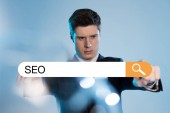 Fotografie handsome businessman in suit pointing at search bar with seo letters in front on blue background