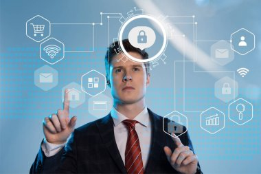 handsome businessman in suit pointing with fingers at cyber security icons in front on blue background