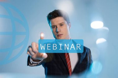 Confident businessman in suit pointing at webinar illustration in front on blue background stock vector